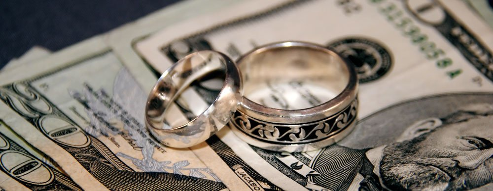 his and her wedding rings on top of stack of money